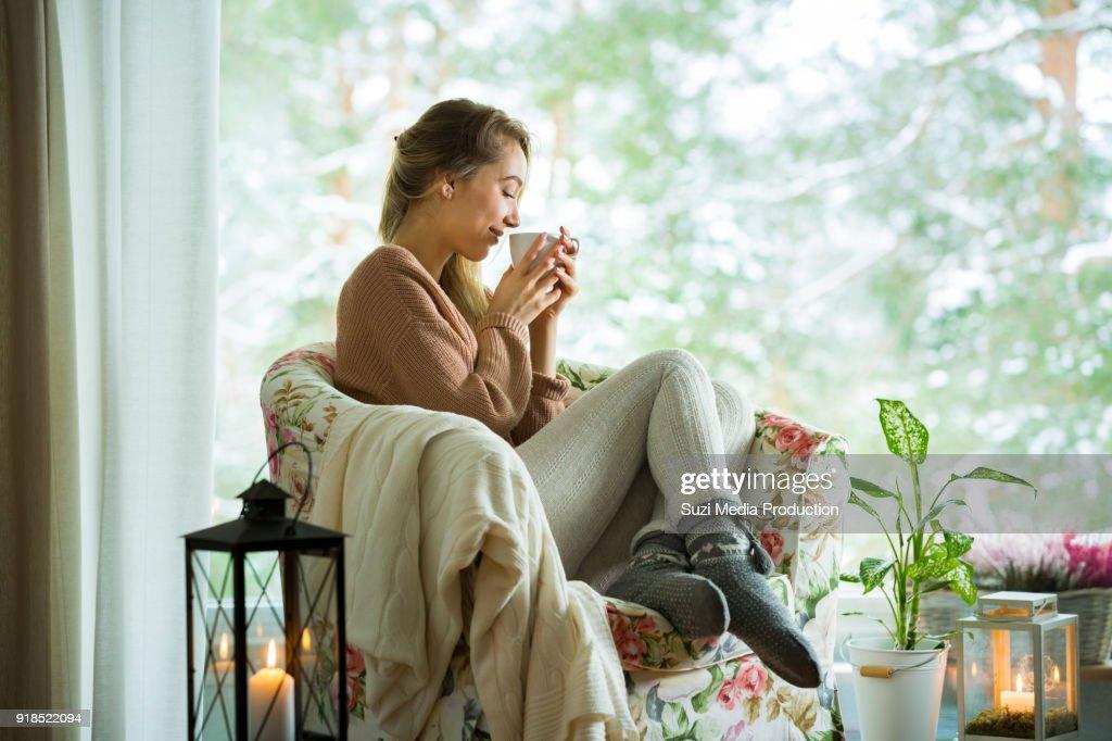 Jonge vrouw door het raam met een kop warme koffie : Stockfoto