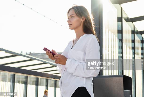 young woman calling on a mobile at train station during early morning. - ukraine stock pictures, royalty-free photos & images