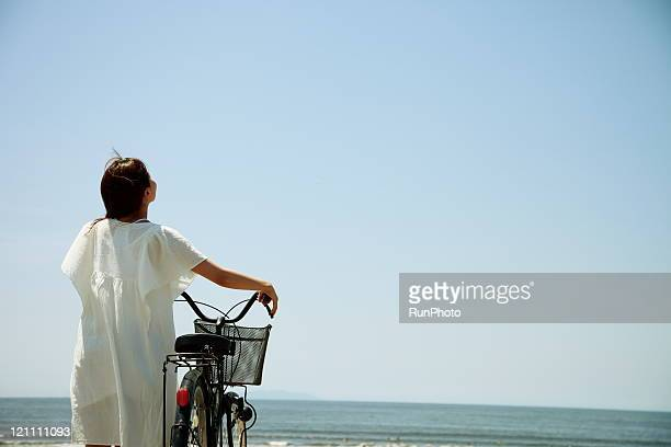 young woman came to the beach by bicycle