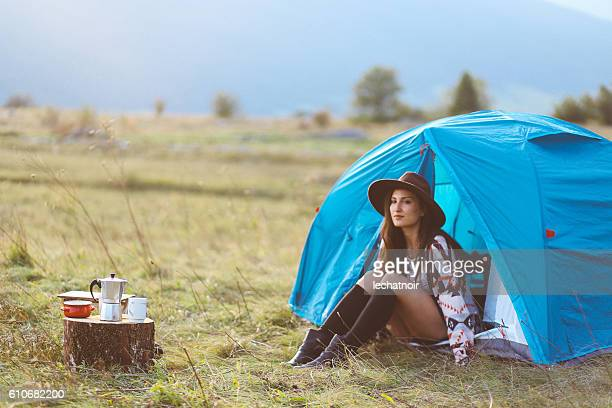 Young woman camping in a tent in sunset