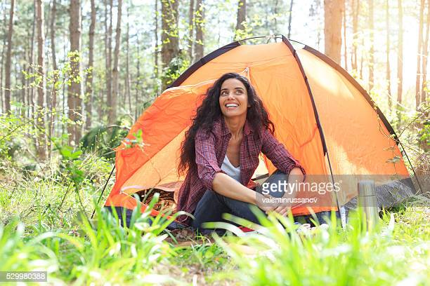 Young woman camping in the forest