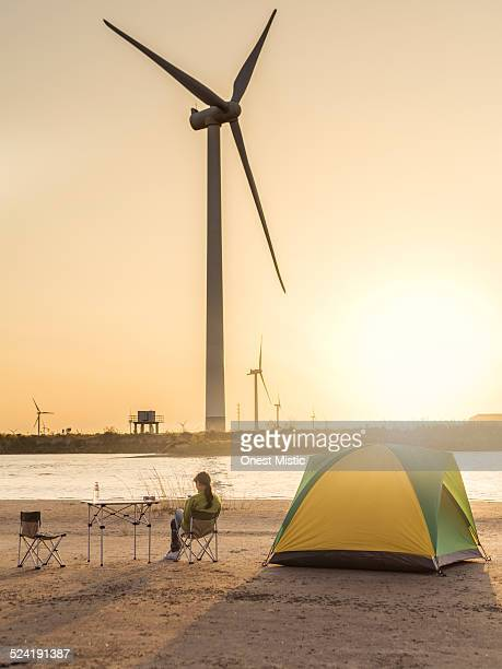 Young woman camping near wind farm.