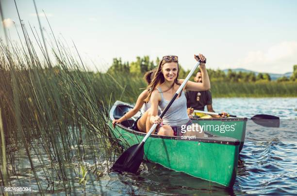 young woman canoeing on the lake - canoeing stock pictures, royalty-free photos & images