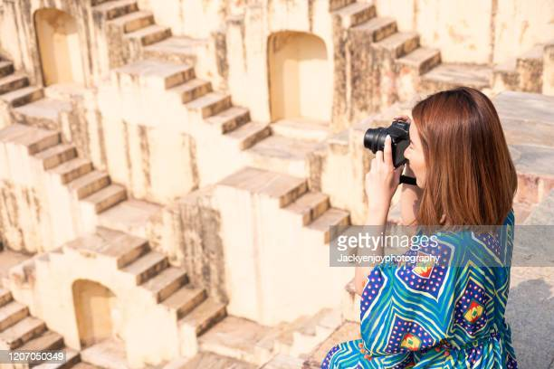 young woman capture photo of chand baori stepwell rajasthan, india - chand baori stock pictures, royalty-free photos & images