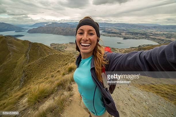 Young woman captures her success of reaching mountain top