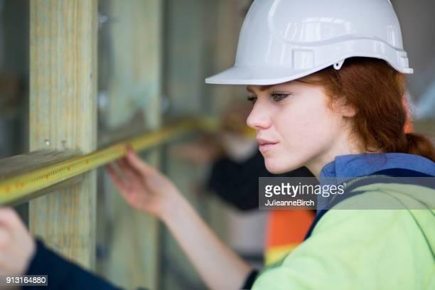 Junge Frau Zimmermann auf der Baustelle mit Maßband messen