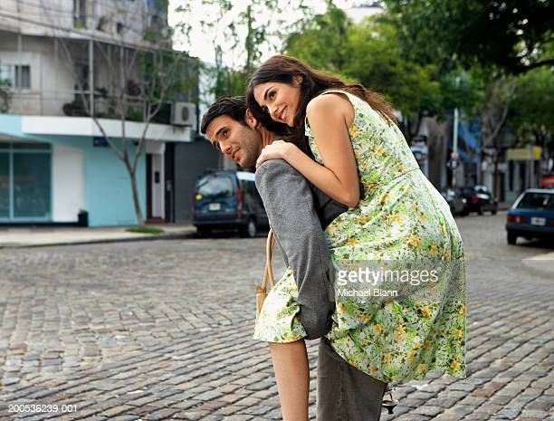 young woman carried piggy back in street, smiling - lying on back stock pictures, royalty-free photos & images