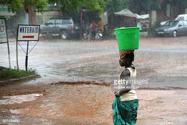 A young woman carries a bucket of water on her head during a downpour on the streets of Bamako during the rainy season The downpours can be...