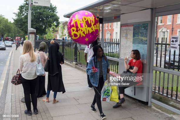 Young woman carries an oversized Happy Birthday balloon for a friend in Camberwell, on 30th May 2018, in London, England.