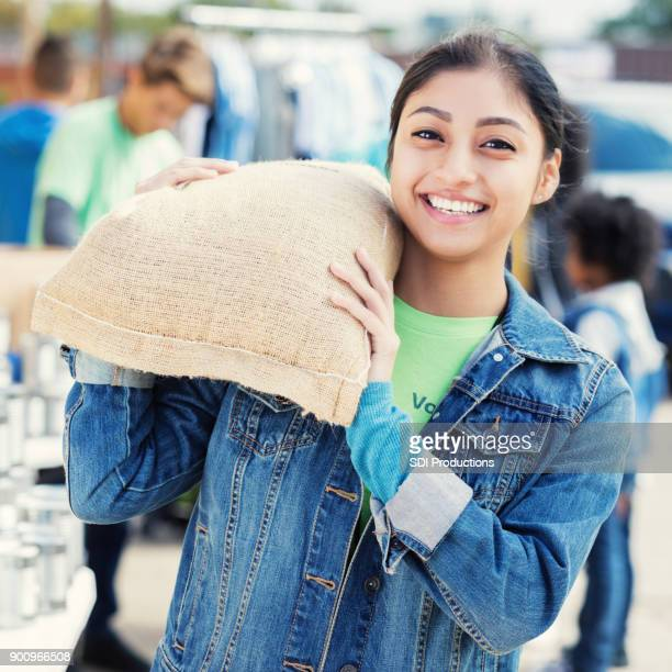 young woman carries bag of heavy food during food drive - humanitarian aid stock pictures, royalty-free photos & images