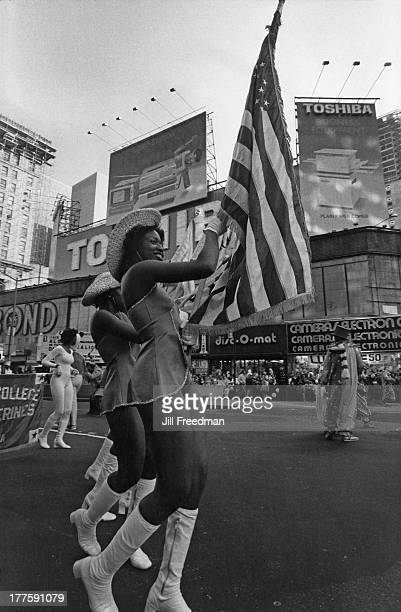 A young woman carries the American flag at a parade in New York City circa 1980