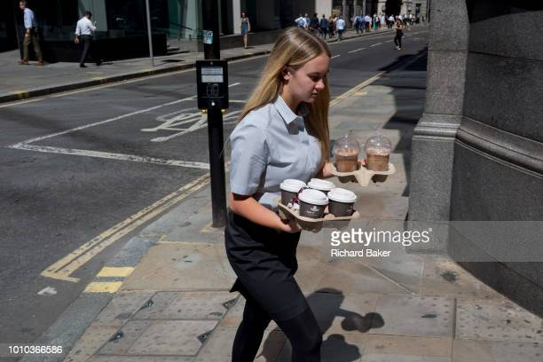 A young woman carries trays of coffees and iced drinks during the 2018 heatwave in the City of London the capital's historic financial district on...