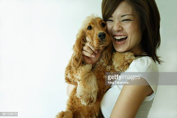 young woman carrying a dog and laughing - cocker spaniel foto e immagini stock