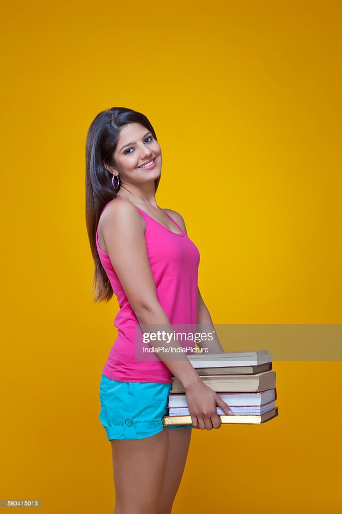 Young woman carrying a pile of books : Stock Photo