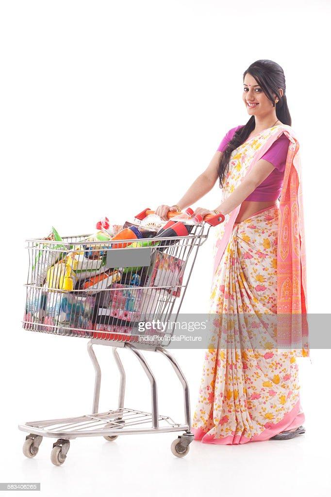 Young woman carrying a shopping cart : Stock Photo