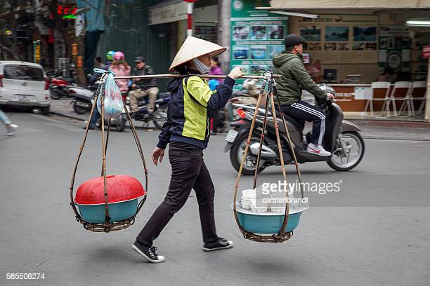Young woman carrying a street kitchen in Hanoi