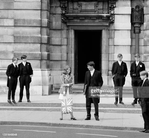 Young woman carrying a Union Jack bag standing with some formally dressed Eton schoolboys during the annual Fourth of June Founder's Day celebrations...