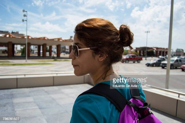 young woman carrying backpack on street in city against sky - ciudad juarez stock photos and pictures