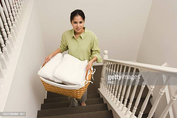 Young woman carrying basket of towels up stairs, elevated view