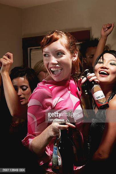 Young woman carrying beer bottles, people dancing around