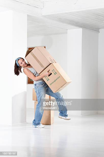 Young woman carrying cardboard boxes