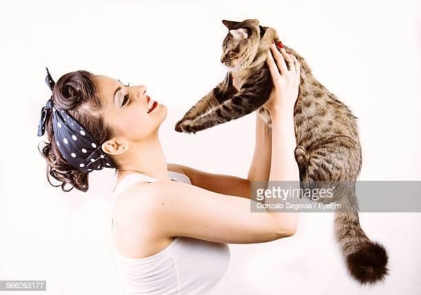 Young Woman Carrying Cat Against White Background