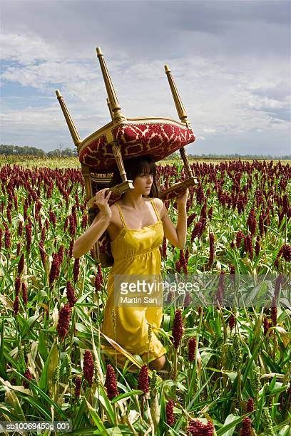 Young woman carrying chair in field