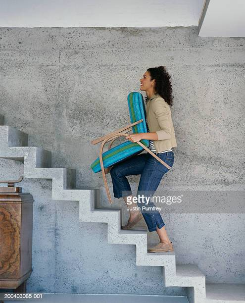 Young woman carrying chair upstairs, side view
