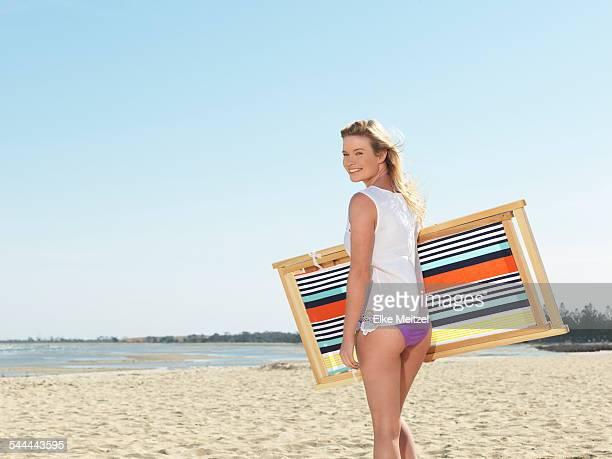 Young woman carrying deck chair on beach, Altona, Melbourne, Victoria, Australia
