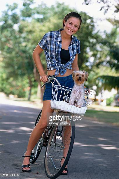Young Woman Carrying Dog in Bicycle Basket