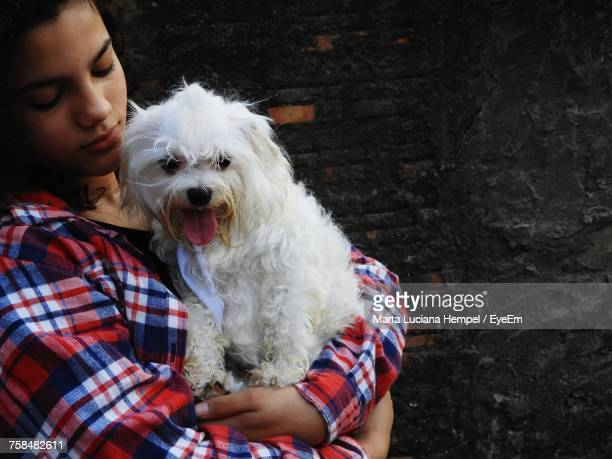 Young Woman Carrying Dog While Standing Against Wall