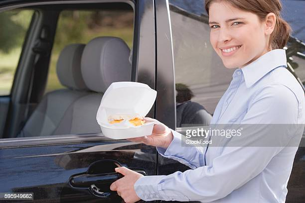 Young woman carrying English muffin in polystyrene box to car