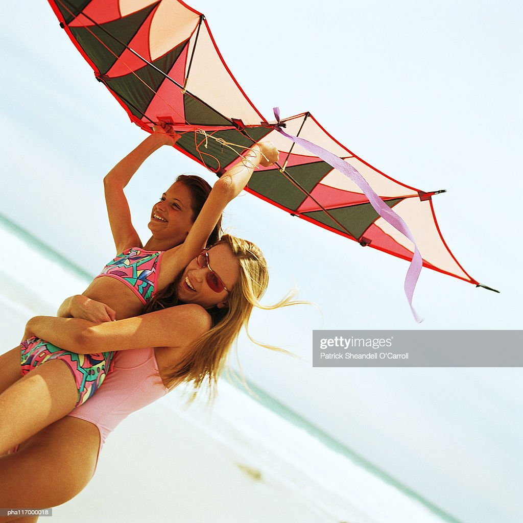 Young woman carrying girl with kite on the beach : Stock Photo