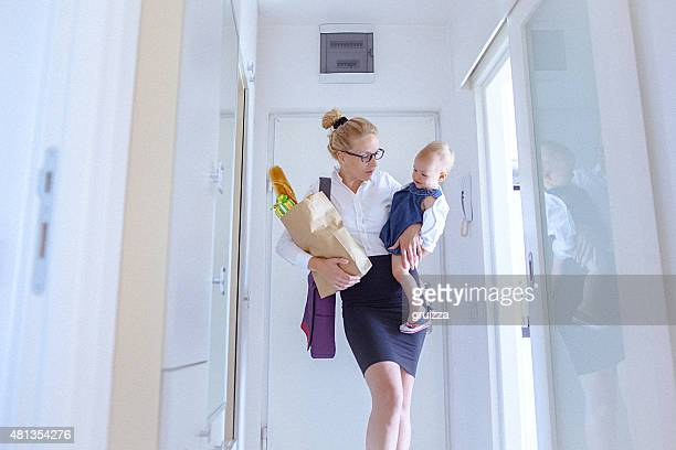 Young woman carrying grocery and a baby girl coming home