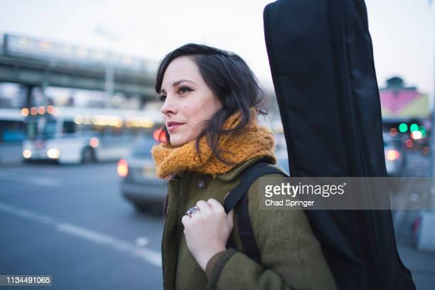 young woman carrying guitar case - guitar case stock pictures, royalty-free photos & images