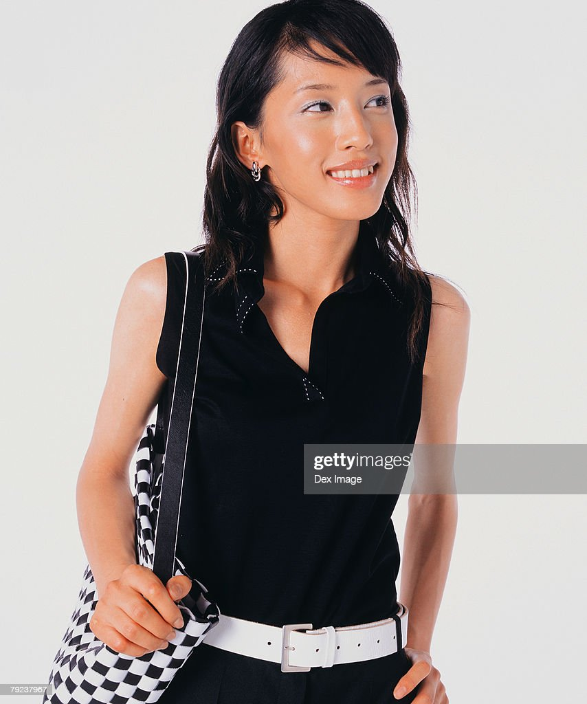 Young woman carrying handbag, hand on hip : Stock Photo