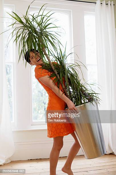 Young woman carrying large pot plant in house, yelling