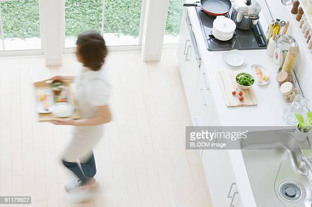 Young woman carrying meal on tray, high angle view, blurred motion