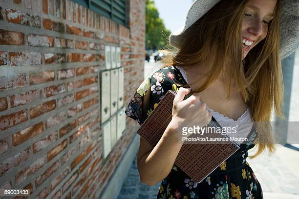 young woman carrying notebook, smiling and looking down - leichter stock-fotos und bilder