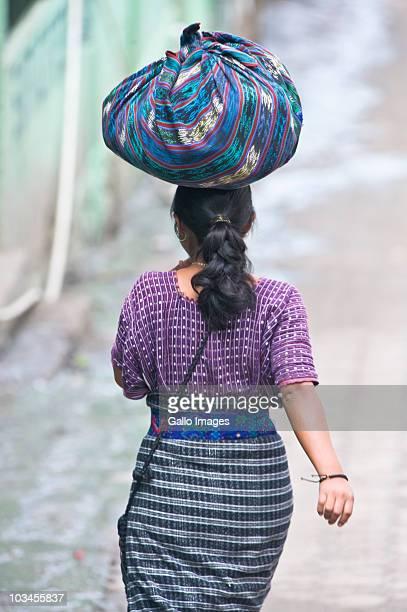 young woman carrying pack on her head, santa catarina, guatemala, latin america - guatemala fotografías e imágenes de stock