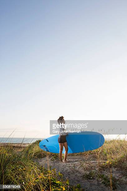 young woman carrying paddle board on beach. - juno beach florida stock pictures, royalty-free photos & images