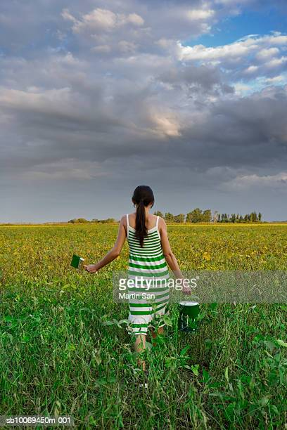 Young woman carrying paint tin in field, rear view