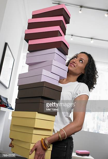 Young woman carrying pile of shoe boxes, smiling