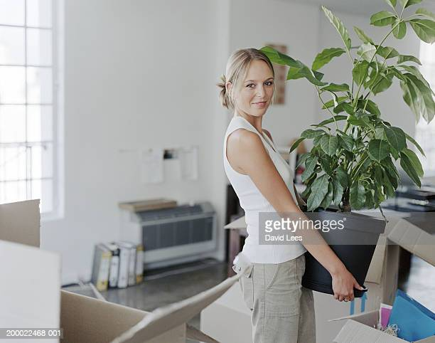 Young woman carrying plant in office, portrait