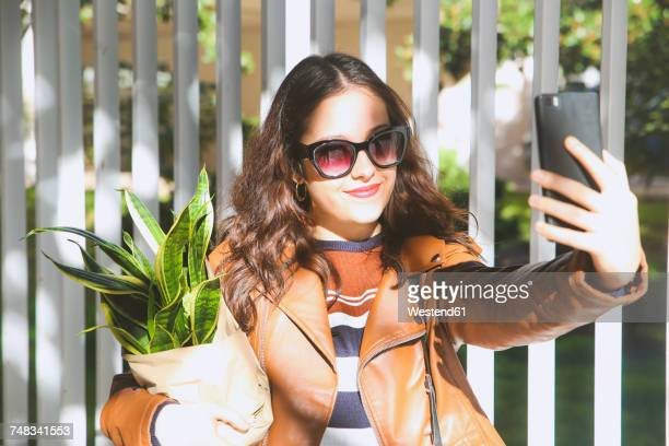 Young woman carrying potted plant taking selfie with smartphone