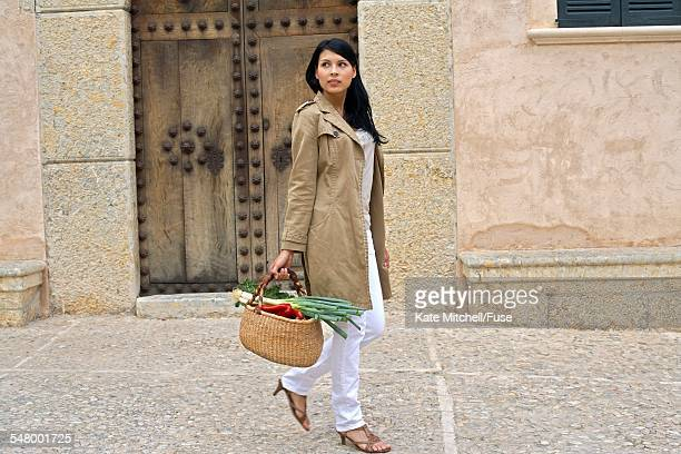 young woman carrying produce in basket - iberian stock photos and pictures
