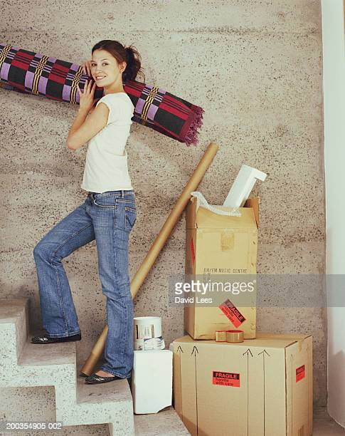 Young woman carrying rolled carpet up stairs, smiling, portrait