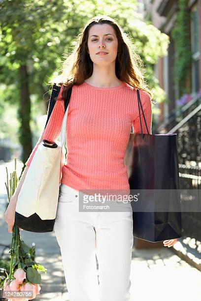 Young woman carrying roses and shopping bags
