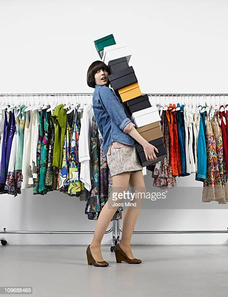 young woman carrying shoe boxes in store - シューズボックス ストックフォトと画像