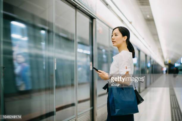 young woman carrying shopping bag using smartphone while waiting for subway in platform - rush hour stock pictures, royalty-free photos & images